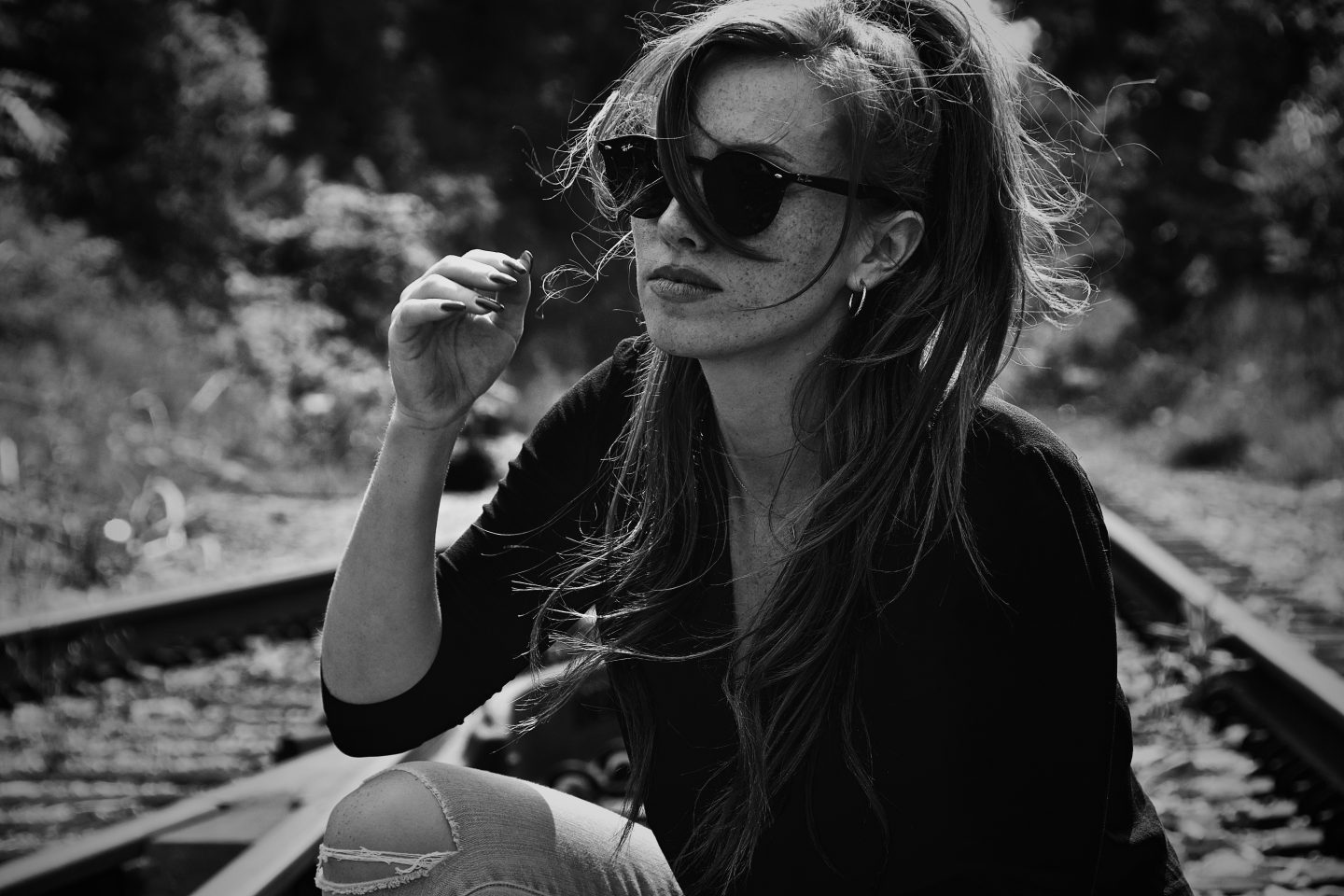 Genevieve sitting on train tracks wearing Ray Ban sunglasses for an editorial shoot for fashion news.